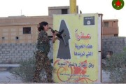 Female Kurdish Fighter Destroys an ISIS Sign Telling Women How to Dress